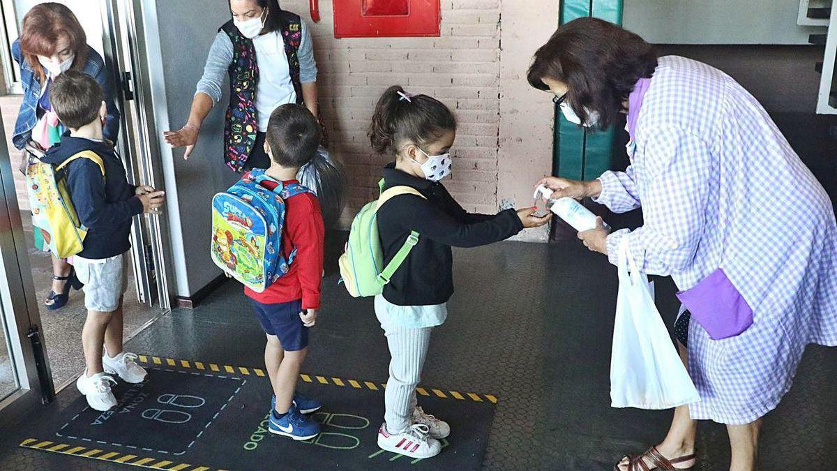 Alumnos se desinfectan las manos a la entrada de un colegio gallego.