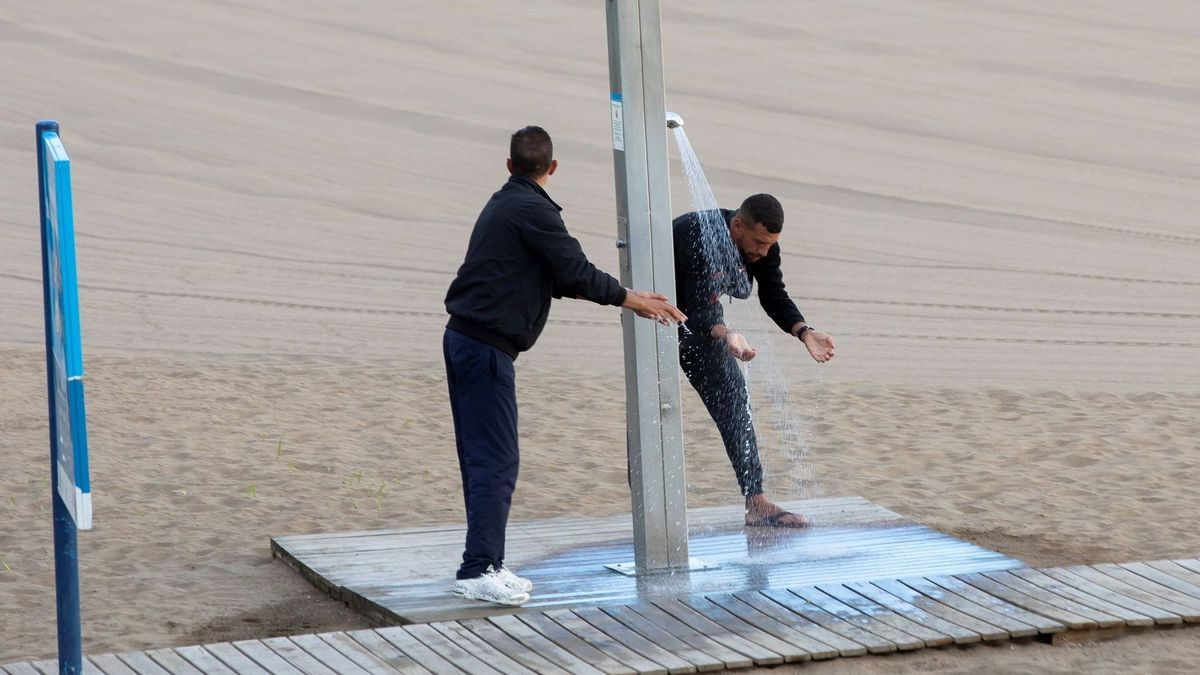 Two migrants wash themselves in a shower on a beach in Las Palmas de Gran Canaria.