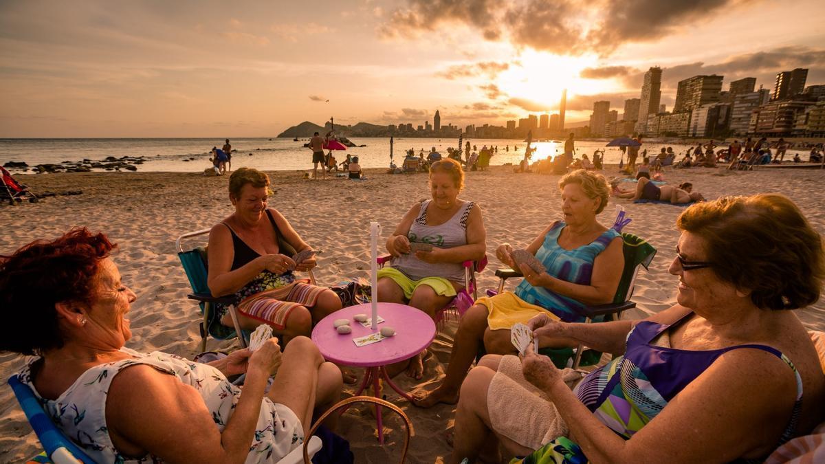Un grupo de mujeres juega a las cartas en un playa valenciana al atardecer.
