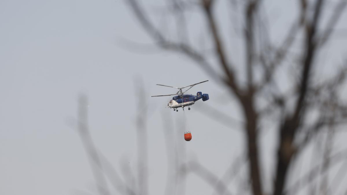 Un helicóptero lleva agua en el incendio de Sierra Bermeja.