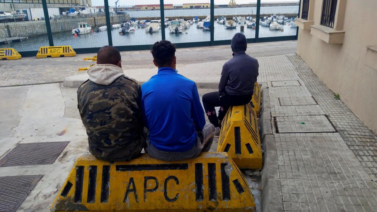 Menores migrantes sentados esperando en un puerto.