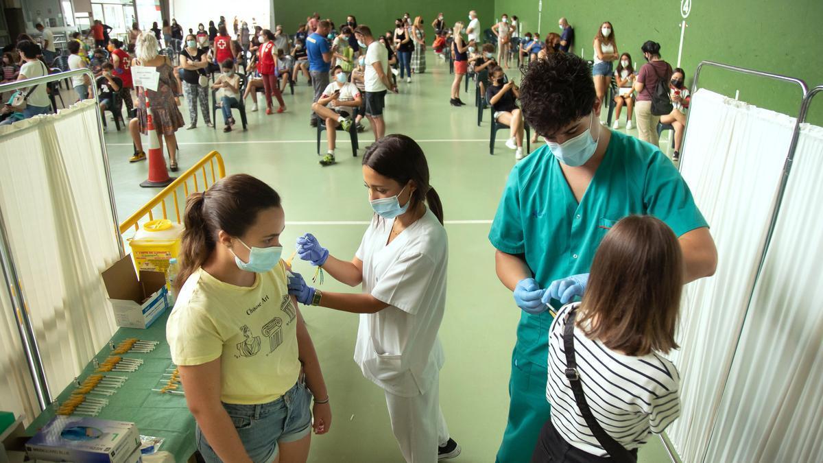 Dos personas se vacunan contra el COVID.