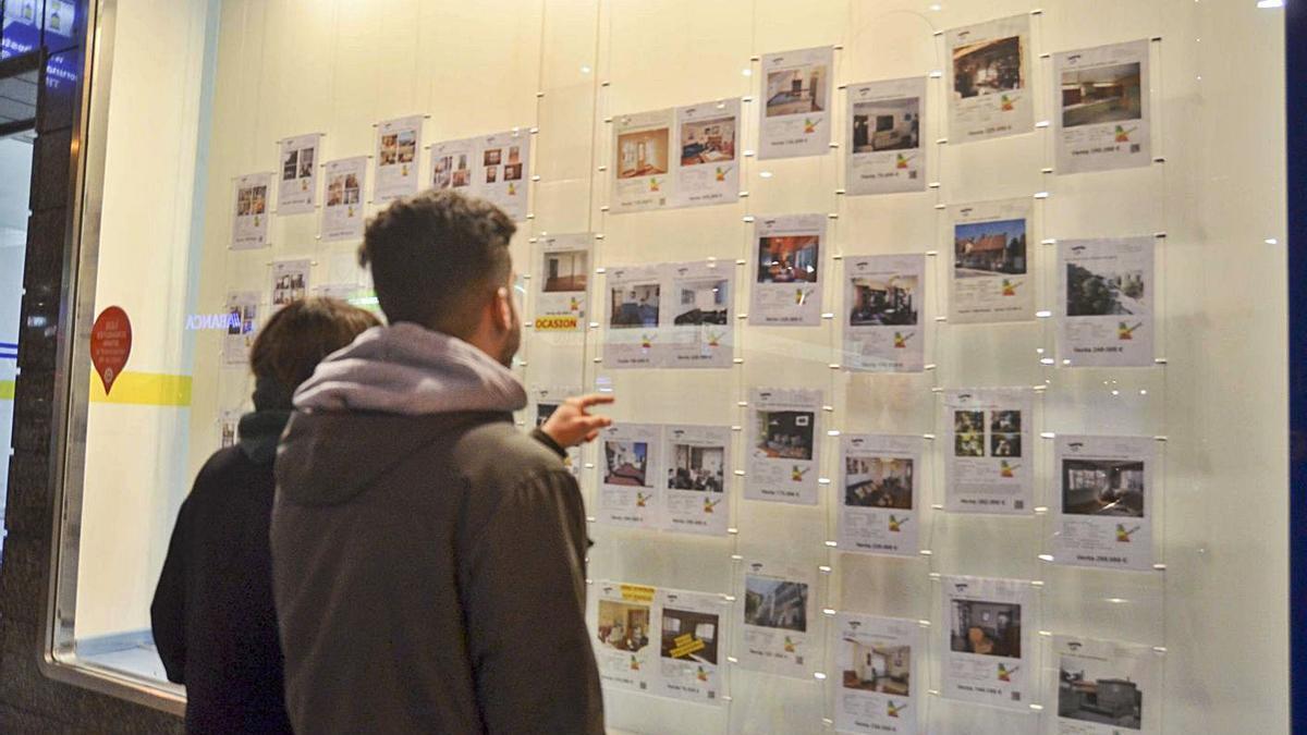 Dos jóvenes observan las ofertas de alquiler en una inmobiliaria.     // L. O.