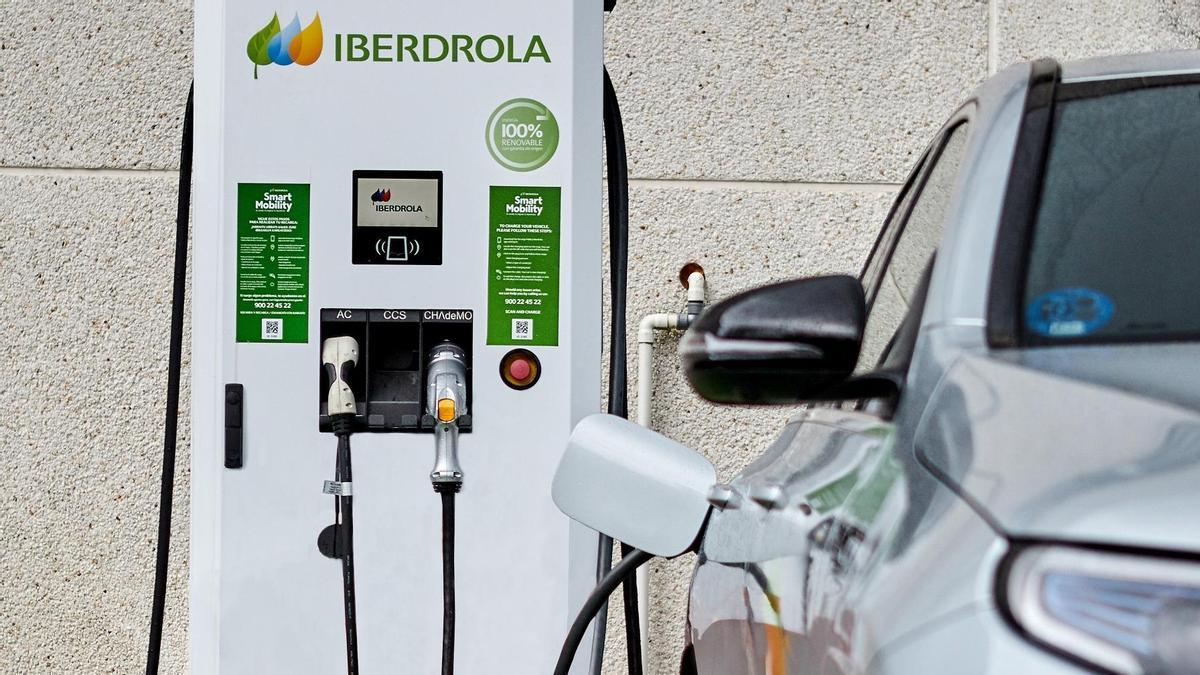 Uno de los múltiples puntos de recarga de vehículos eléctricos de Iberdrola y la app donde buscarlos.