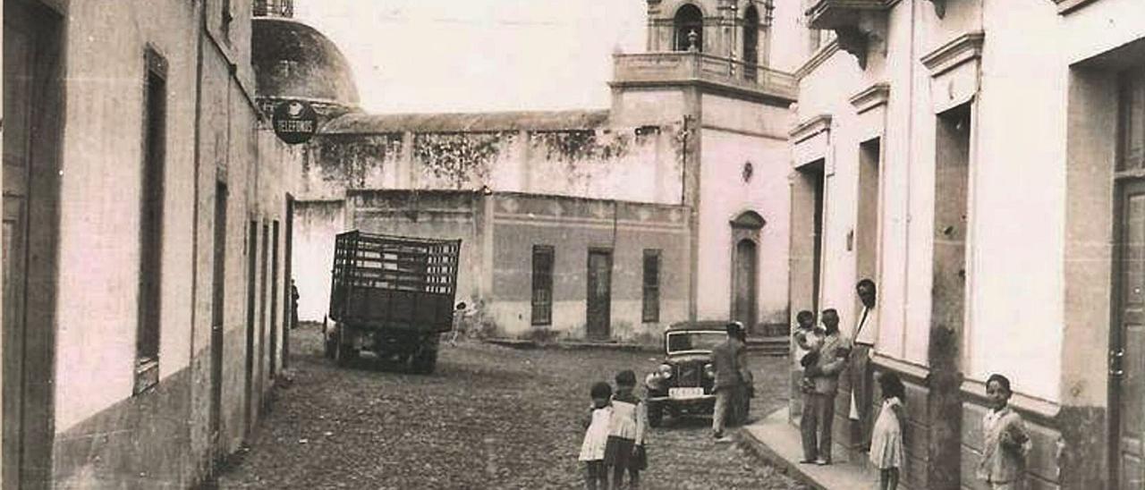 La iglesia del Buen Suceso, al fondo, y tres adultos y cinco menores  en una calle en la década de los años 30 en Carrizal, en la villa de Ingenio | | SUÁREZ ROBAINA