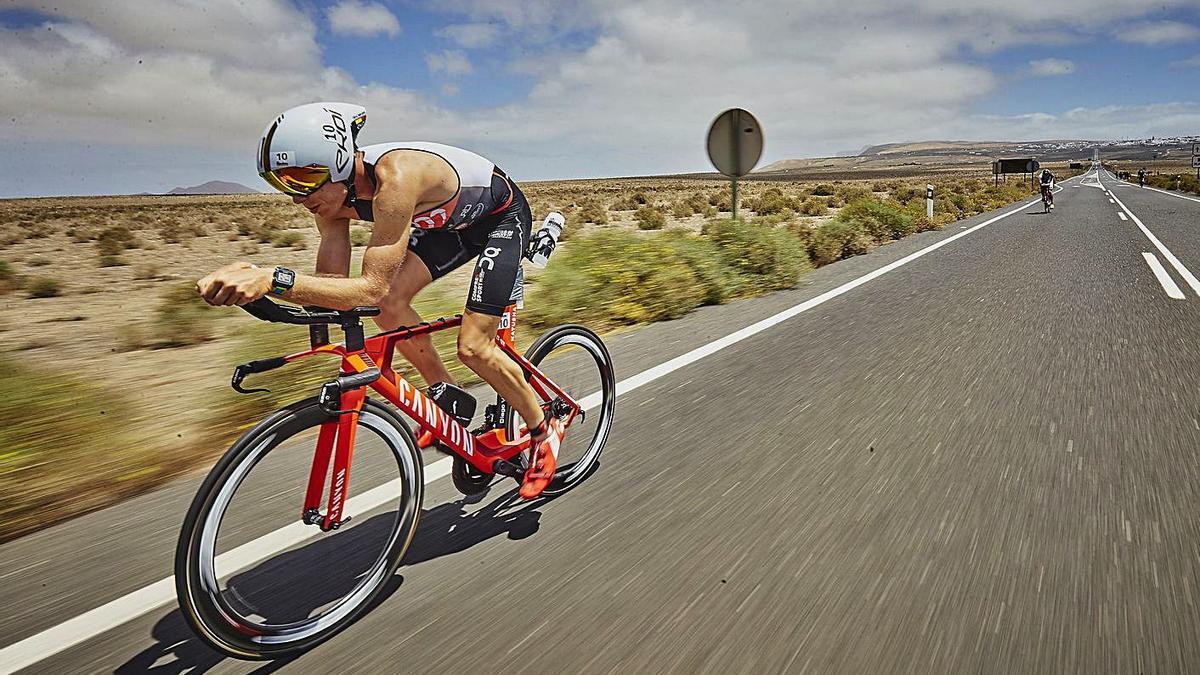 Un triatleta del Ironman Lanzarote durante la prueba de ciclismo en una edición pasada, por una carretera lanzaroteña. | | LP/DLP