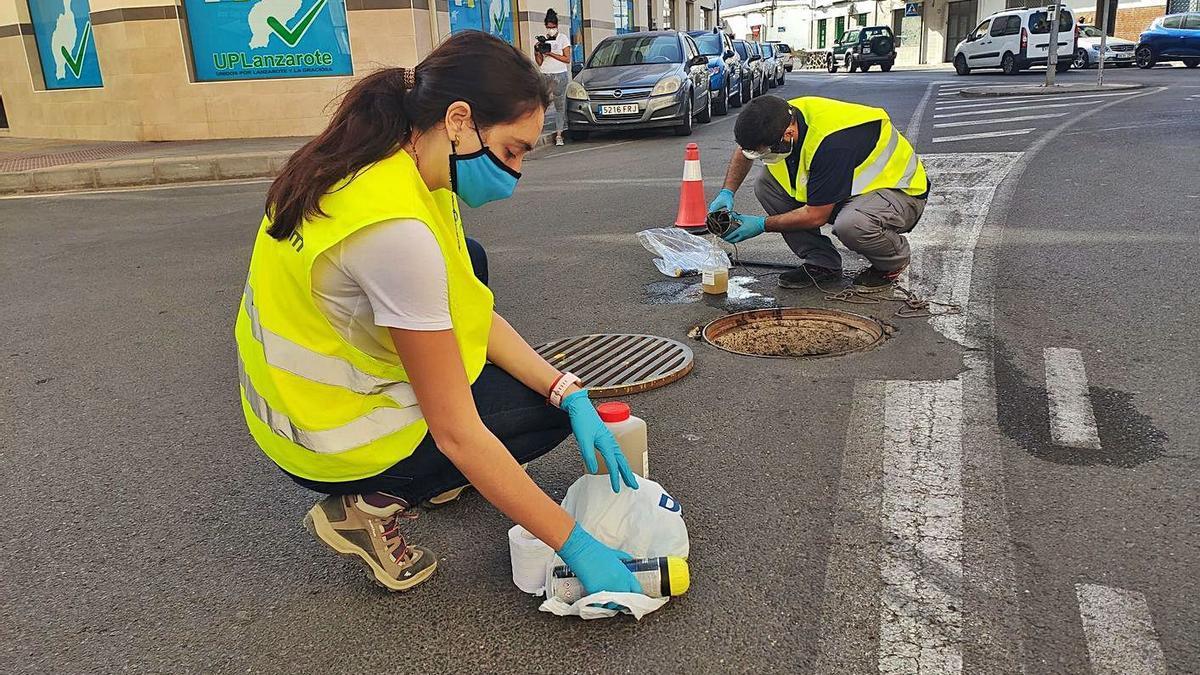 Dos técnicos recogen muestras de aguas residuales en Lanzarote.