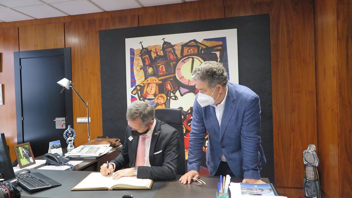 El delegado del Gobierno en Galicia, José Miñones, firma en el libro de honor del Concello junto al alcalde, Miguel Lores