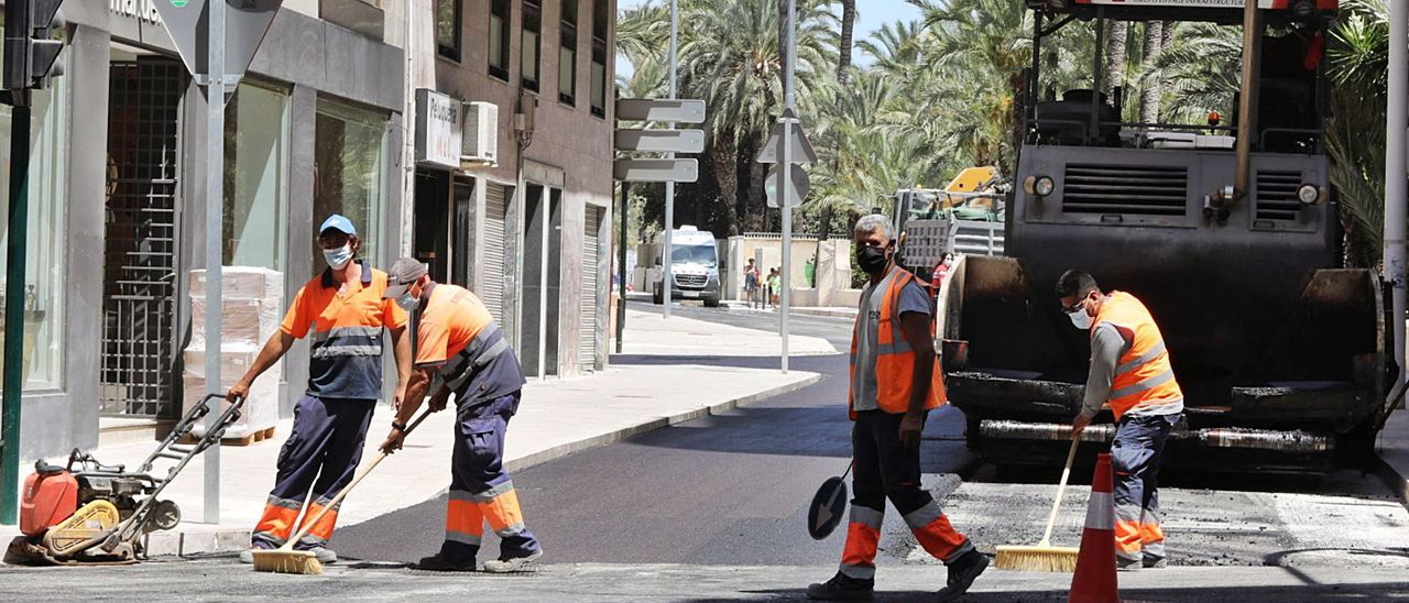 Los trabajos de asfaltado en la calle Virgen de la Cabeza retomados este jueves tras abandonar la empresa la obra en mayo.   ANTONIO AMORÓS