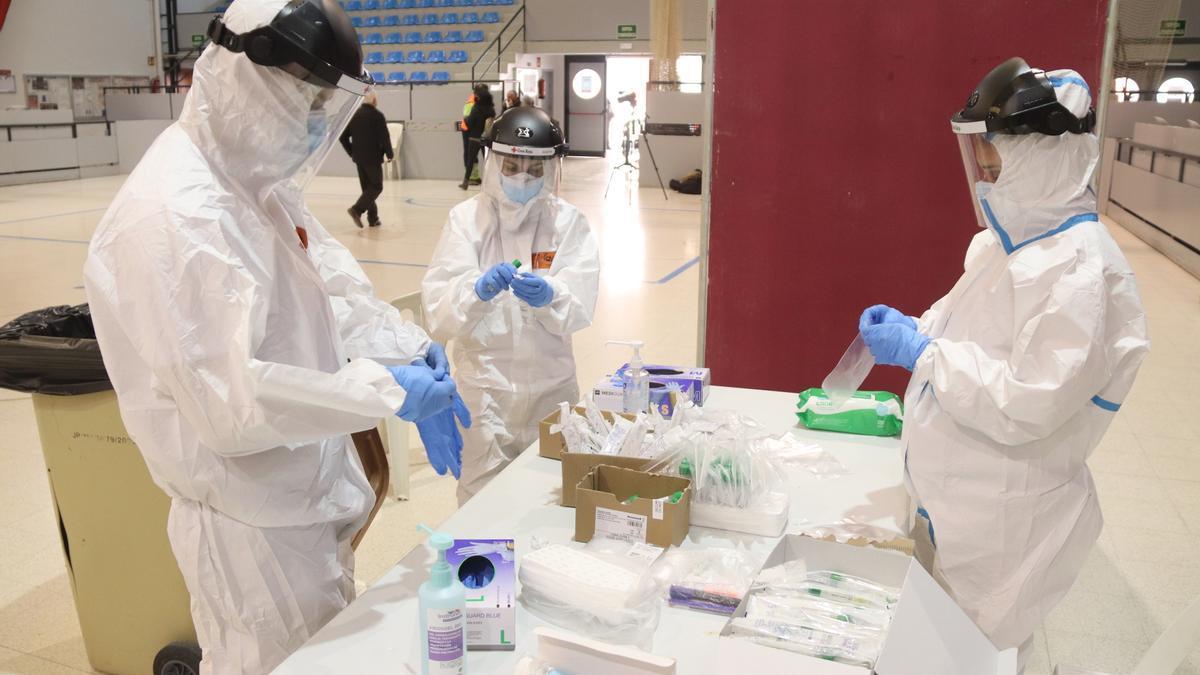 Tres sanitaris preparant el material per fer proves PCR.