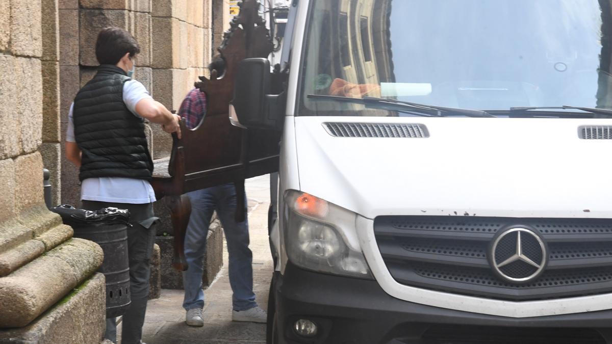 Dos hombres cargan un mueble de la Casa Cornide en una furgoneta.