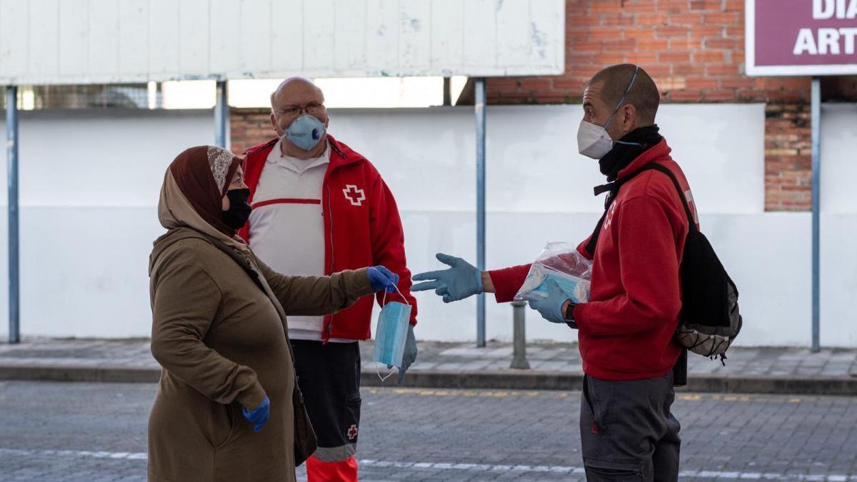 Voluntaris de la Creu Roja repartint mascaretes a Figueres.
