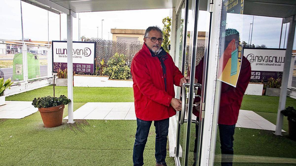 El hostelero Jesús Terol escenifica el cierre de la puerta del local de Lluna Events en Xàtiva. | PERALES IBORRA