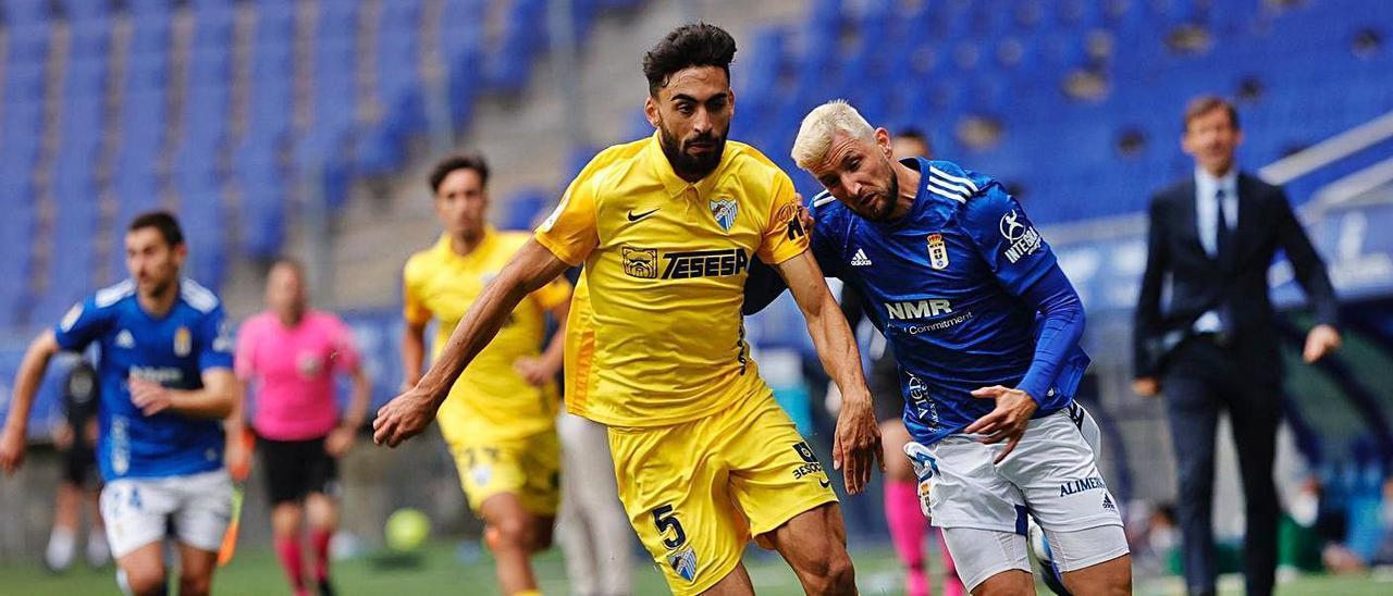 Borja Valle, a la derecha, trata de marcharse del jugador del Málaga Juande. |