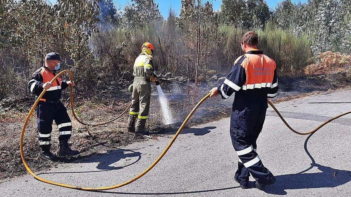 Voluntarios de Protección Civil de Cotobade colaboran para sofocar uno de los fuegos.