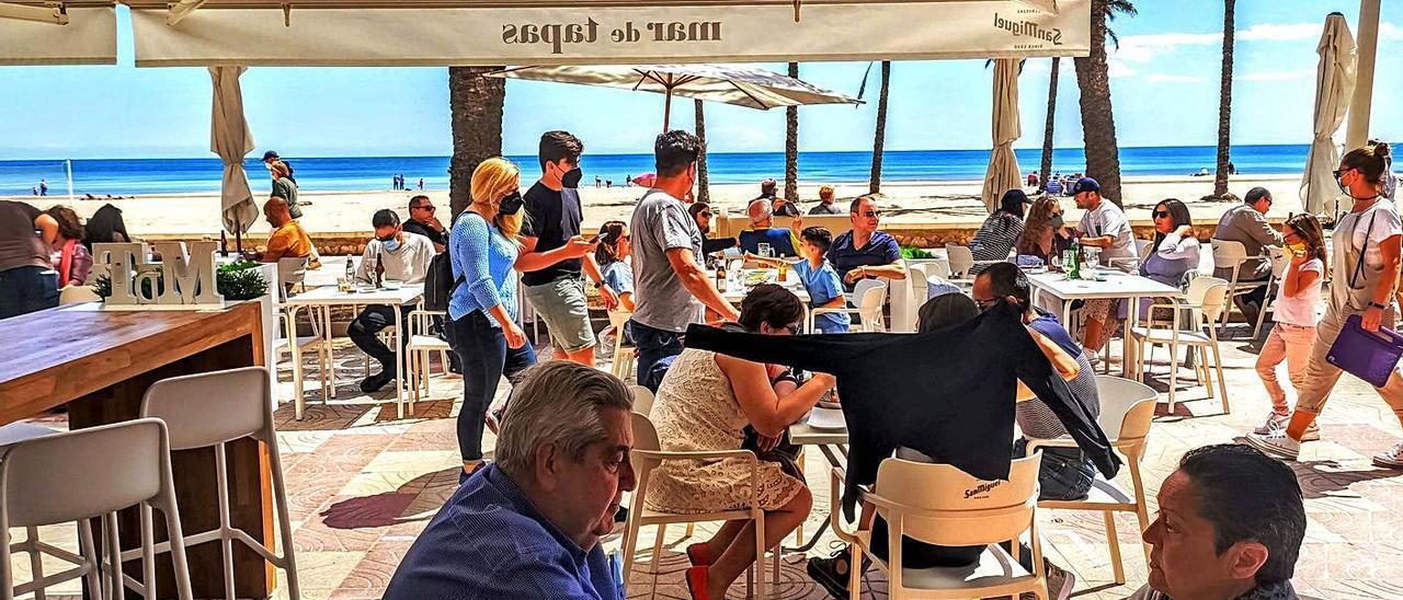 Una terraza del paseo marítimo de Cullera llena de clientes.   JOAN GIMENO