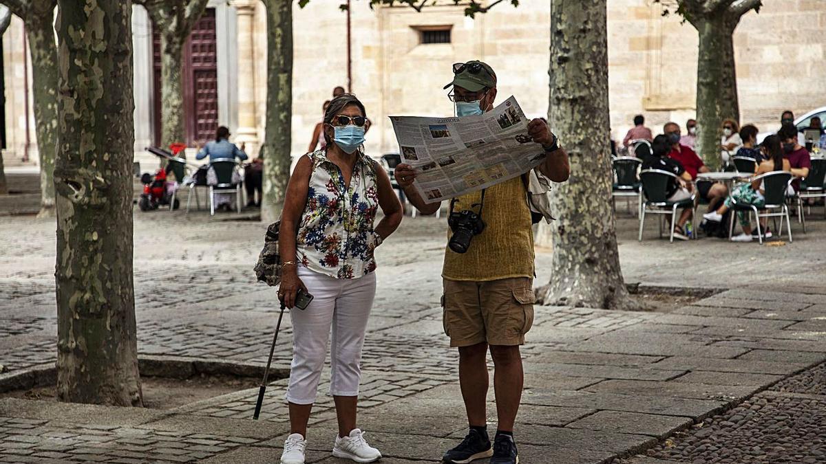 Dos turistas observan un plano de Zamora en la plaza de Viriato. | Nico Rodríguez