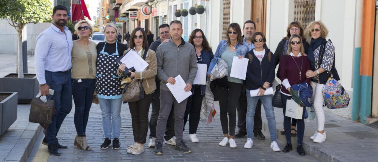 Un grupo de comerciantes de la calle Pintor Picasso exhibe las firmas que están recogiendo para que ni se plantee ni se lleve a cabo la peatonalización del vial.