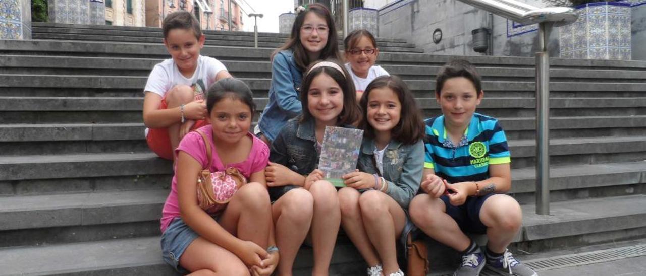 Por la izquierda, arriba, Colás Guitián, Claudia Barragán y Antía Rodríguez. Abajo, Claudia Suárez, Marta Barragán, Alba González y Simón Fernández, en las escaleras de la iglesia de Candás con su libro.