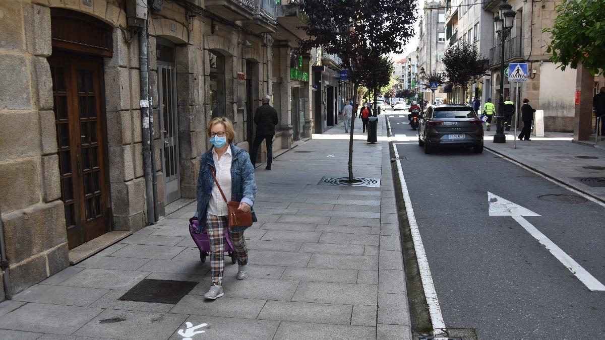 Una mujer camina por una acera de Redondela señalizada con una dirección única.