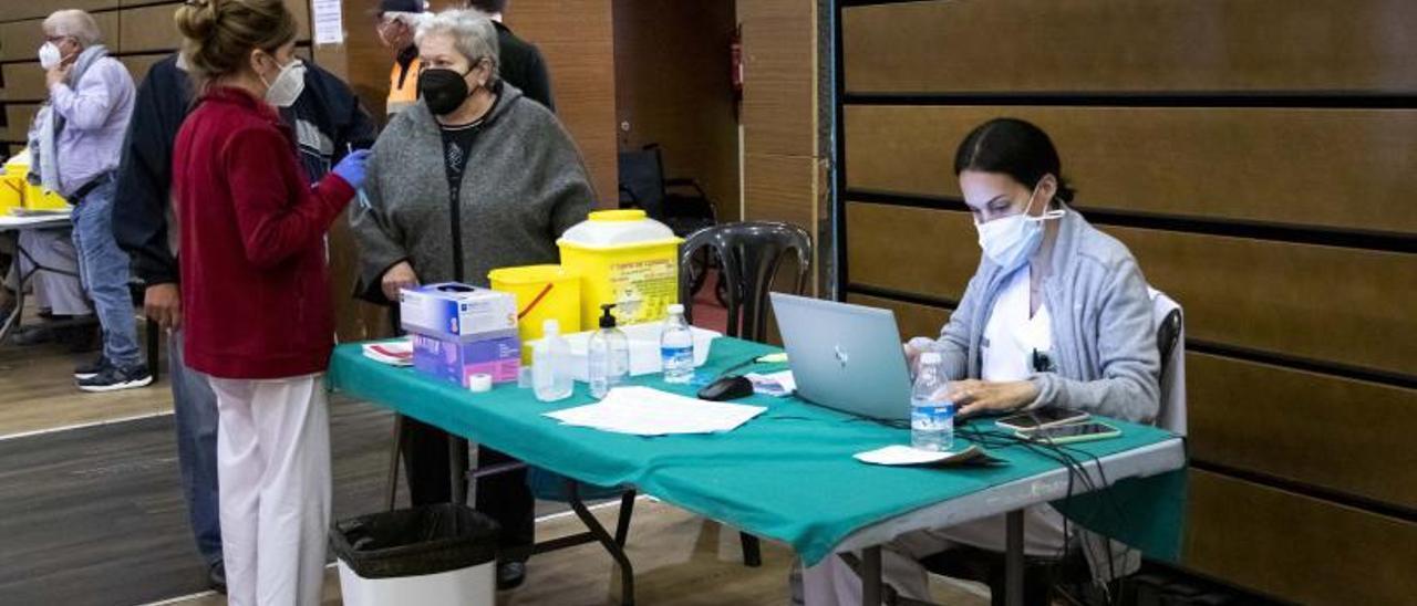 A la izquierda, una enfermera habla con una mujer que va a vacunarse. A la derecha, dos sanitarias preparan las jeringas con las dosis del antídoto. | DANI MONLLOR