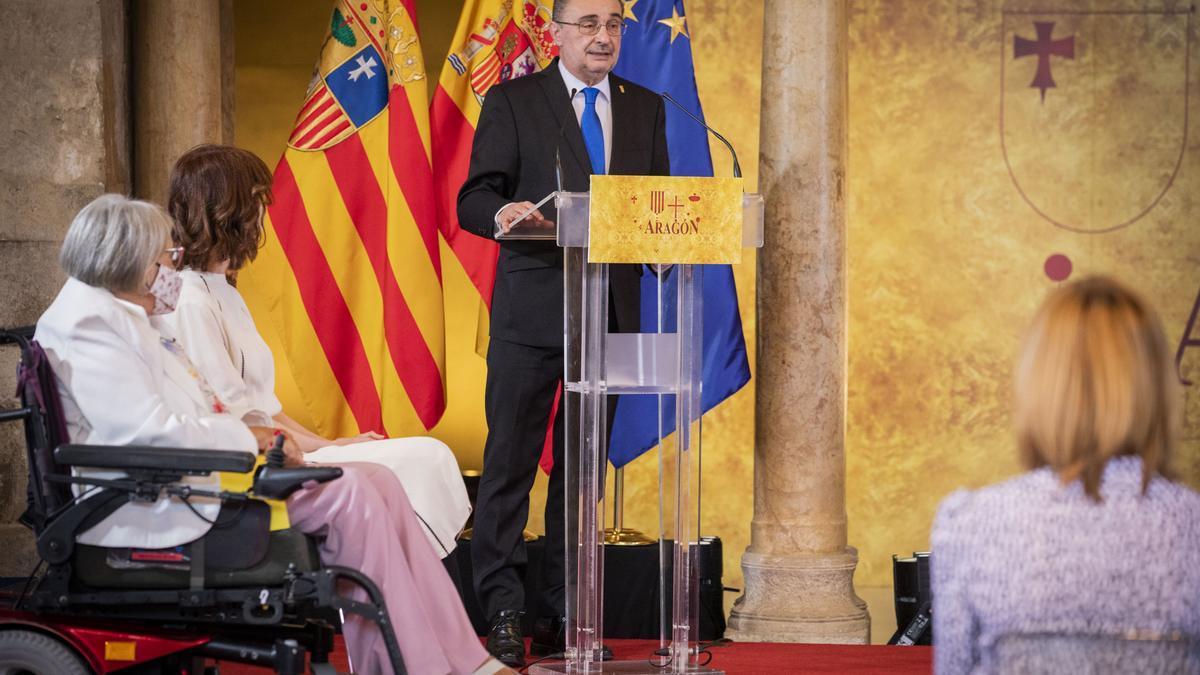 El presidente aragonés, Javier Lambán, durante su discurso de este viernes en La Aljafería, ante la atenta mirada de Irene Vallejo, Premio Aragón 2021, y Emilia Nájera, Premio de las Cortes.