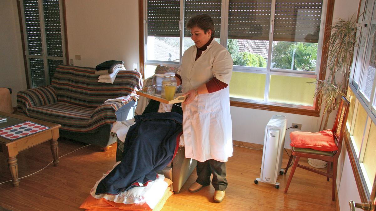 Una empleada del servicio de Ayuda a Domicilio atendiendo a una mujer dependiente en su casa.