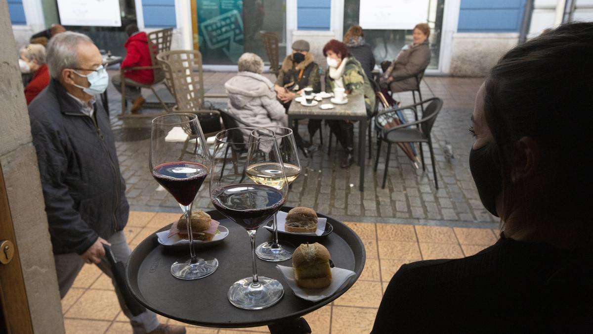 Una camarera se dispone a servir en una terraza de un restaurante.