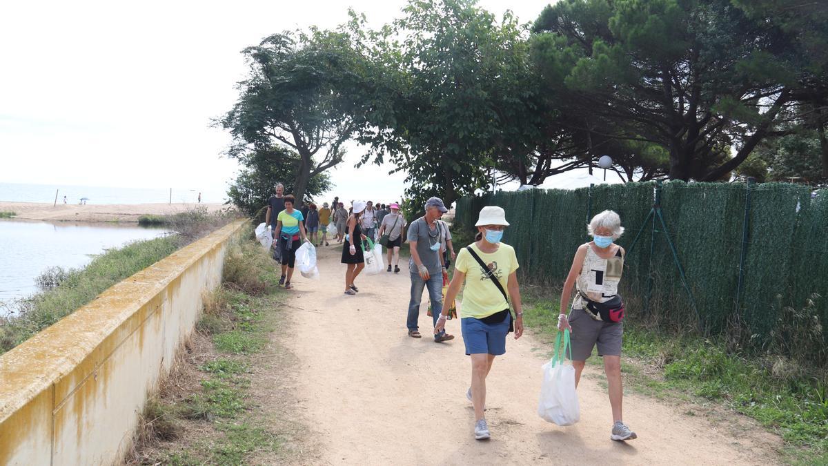 Pla general de diversos voluntaris estrangers participant en una recollida d'escombraries a la desembocadura de Ridaura