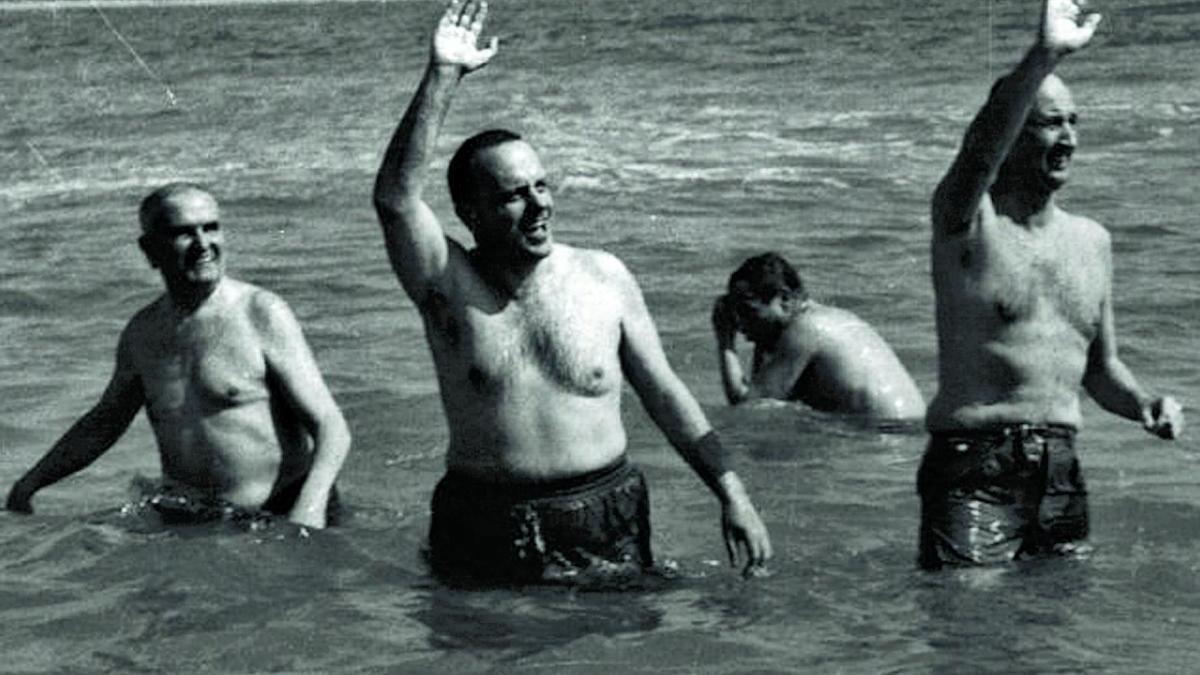 el bany més famós de Manuel Fraga, l'any 1966 a Palomares. 1 El llavors ministre d'Informació i Turisme, al centre de la imatge, saluda en banyador al costat de l'ambaixador americà a Espanya, Angier Biddle Duke, que també aixeca el braç.