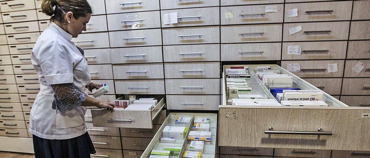 Una farmacéutica busca un medicamento en el almacén de una botica de Alicante.  