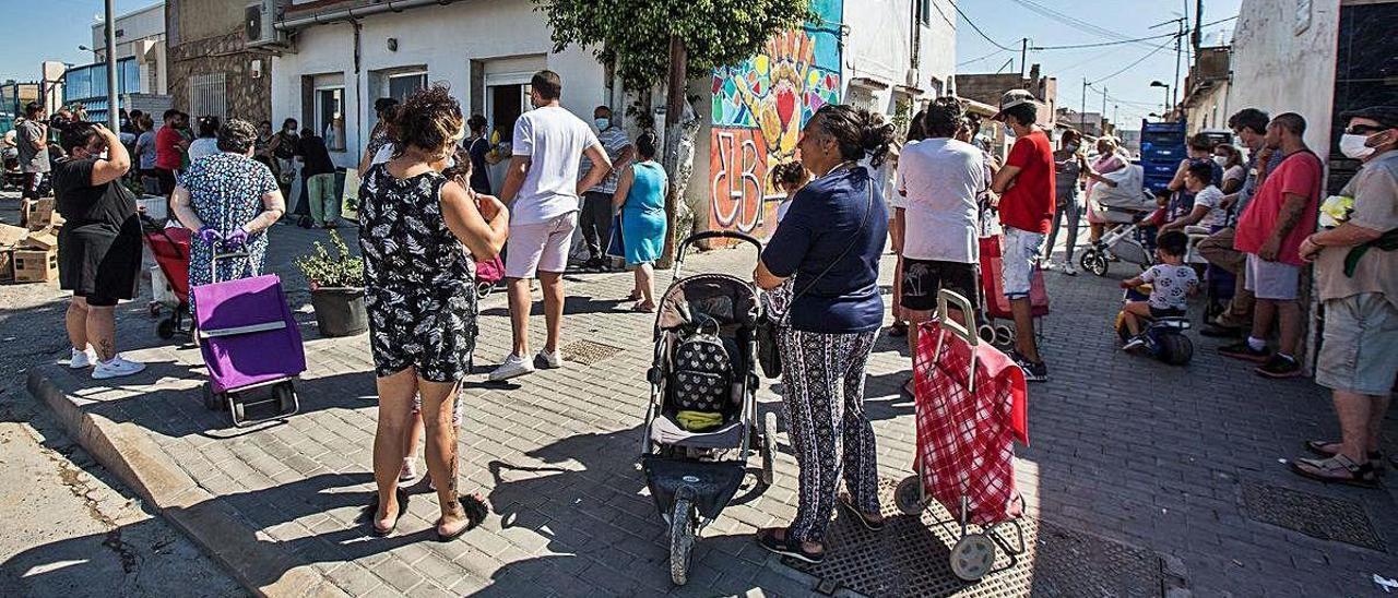 Vecinos del barrio del Cementerio de Alicante hacen cola para recibir comida.