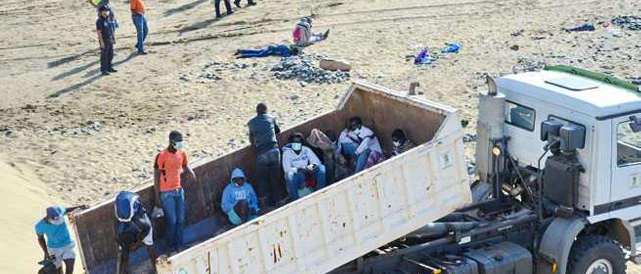 Los inmigrantes suben al camión de Limpieza de San Bartolomé de Tirajana para ser transportados a comisaría.