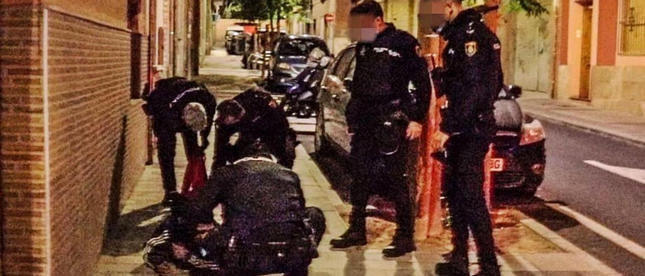 La Policía atiende al hombre apuñalado en el lugar de la agresión.