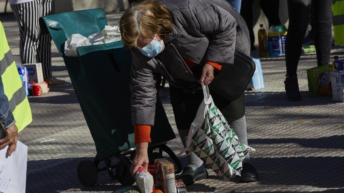 Una mujer recoge productos de alimentación donados.