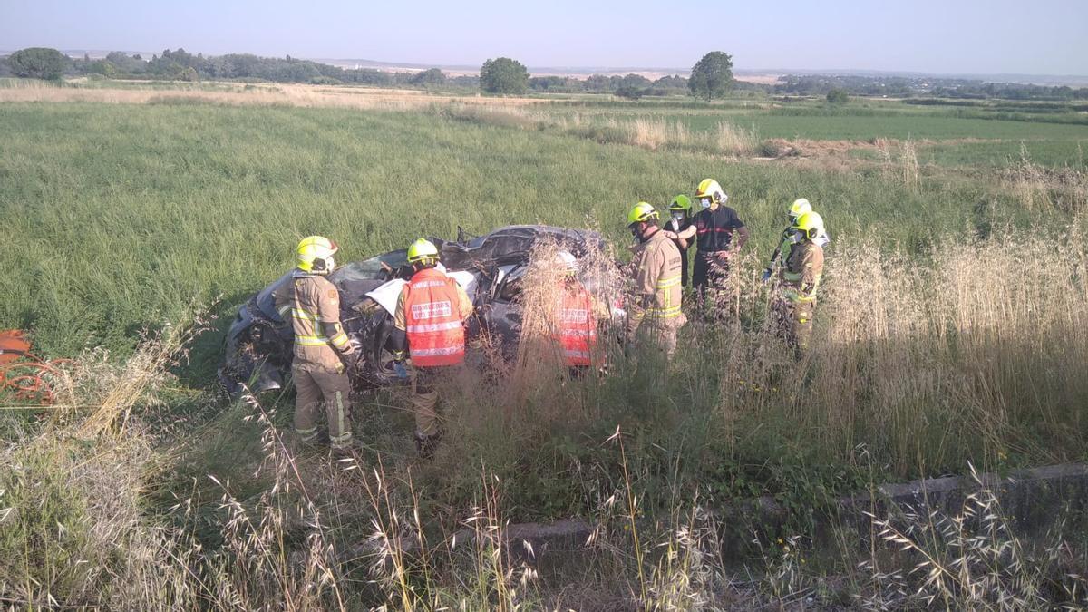 Los bomberos rodean el vehículo en el lugar del accidente.