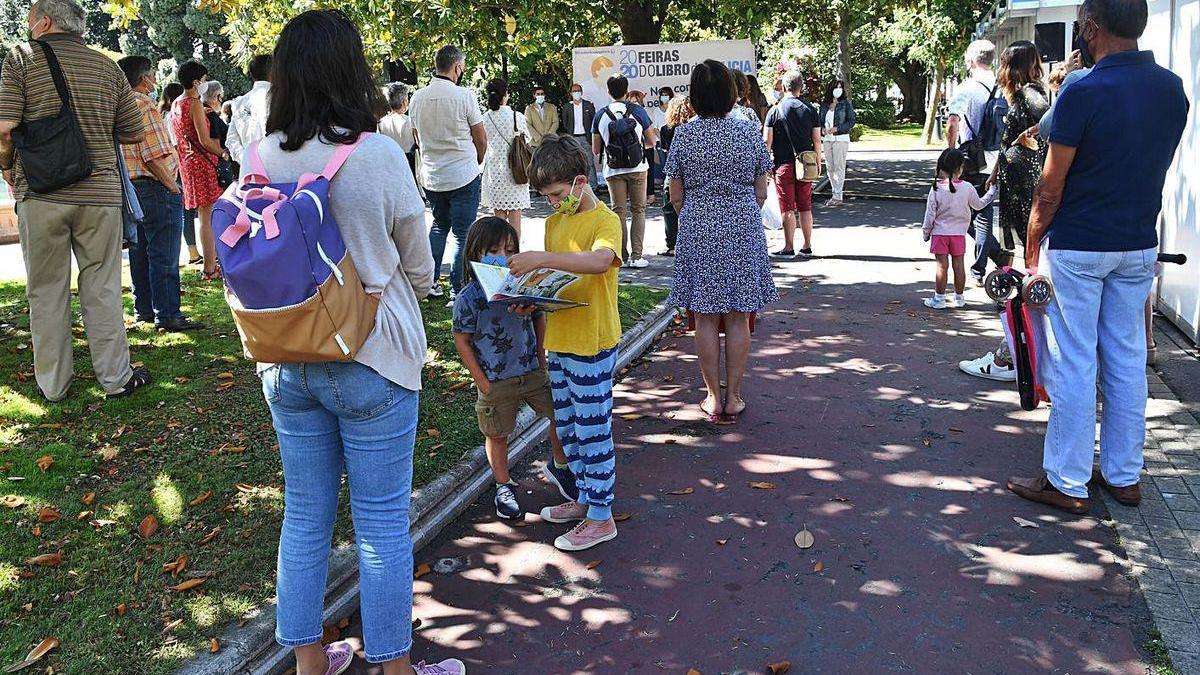 Niños y mayores cumplen las medidas de seguridad en la Feria del Libro de A Coruña.
