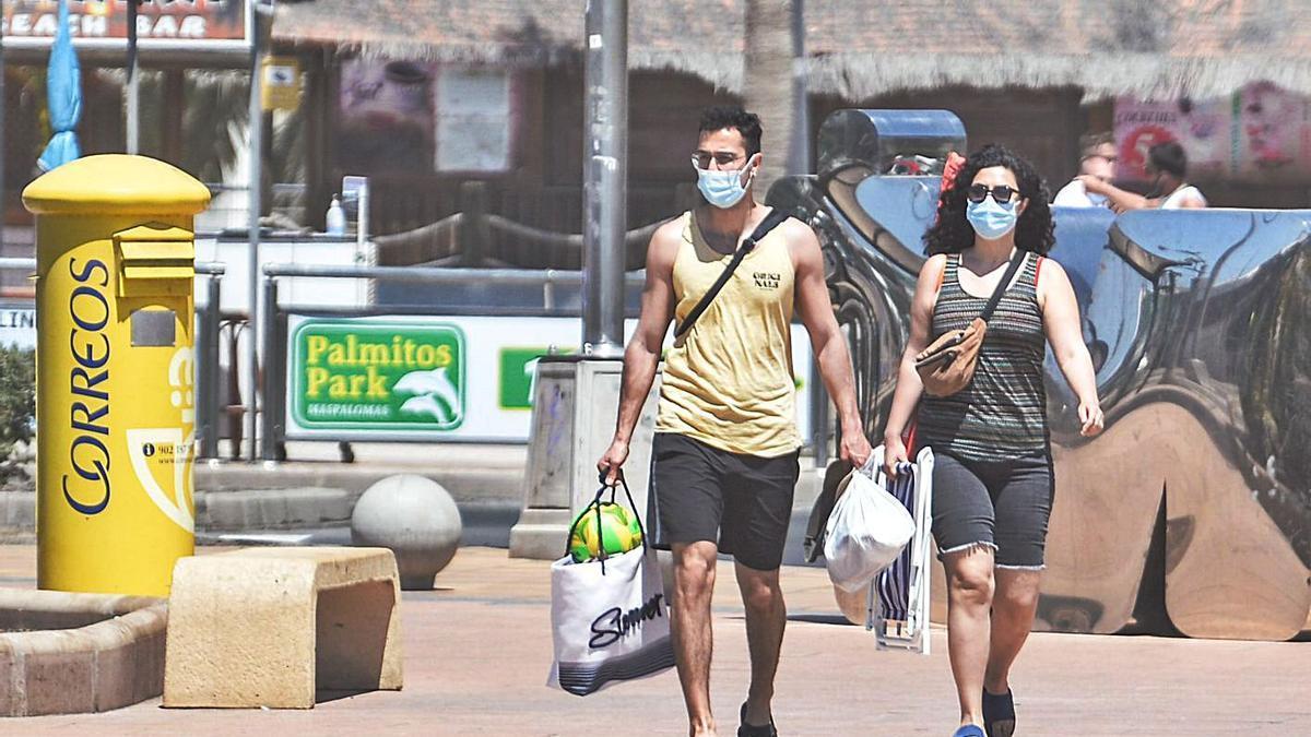 Una pareja de turistas camina con mascarilla.