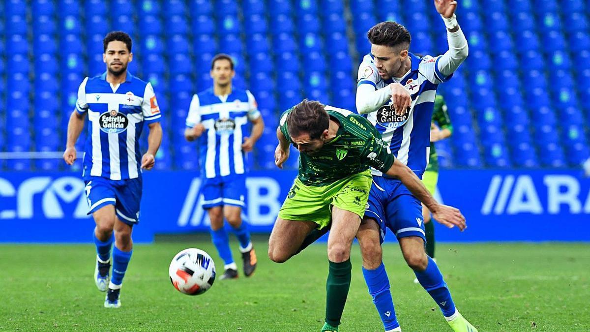 Rayco lucha por el balón con un rival del Guijuelo sobre el césped de Riazor. |  // CARLOS PARDELLAS