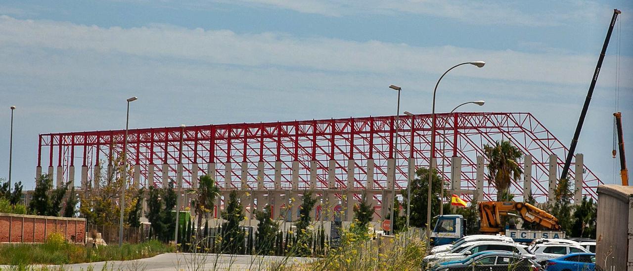 La nave cerrada para el tratamiento de los graneles que se mueven en el puerto de Alicante, de la que ya se ve la estructura, será completamente automatizada.   RAFA ARJONES