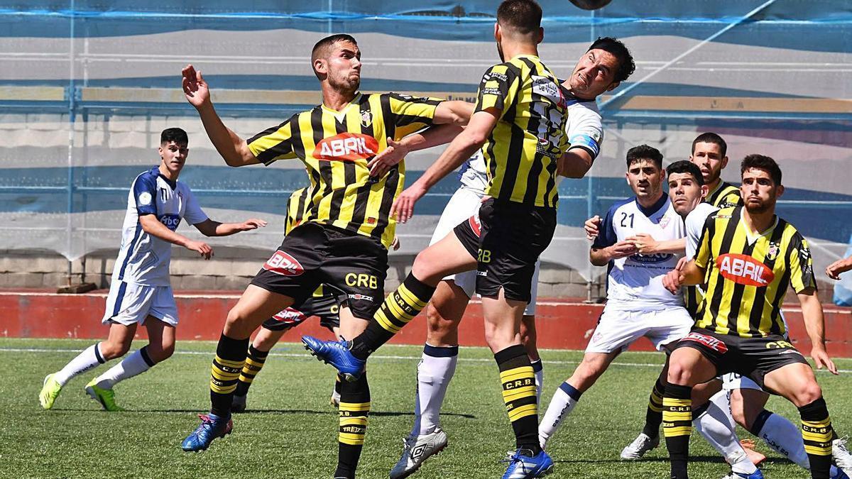 Un jugador del Silva intenta rematar entre dos del Rápido de Bouzas. |  // VÍCTOR ECHAVE