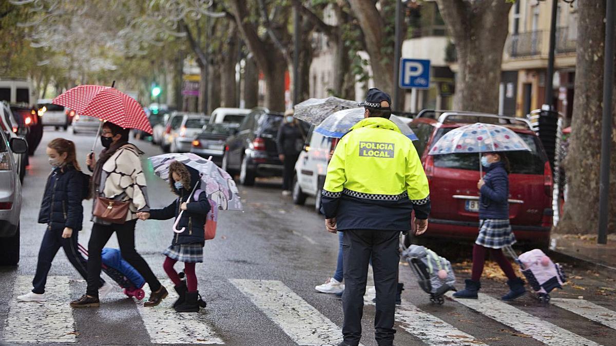 Niños y adultos con mascarilla pasan por un paso de peatones de Xàtiva, ayer por la mañana   PERALES IBORRA