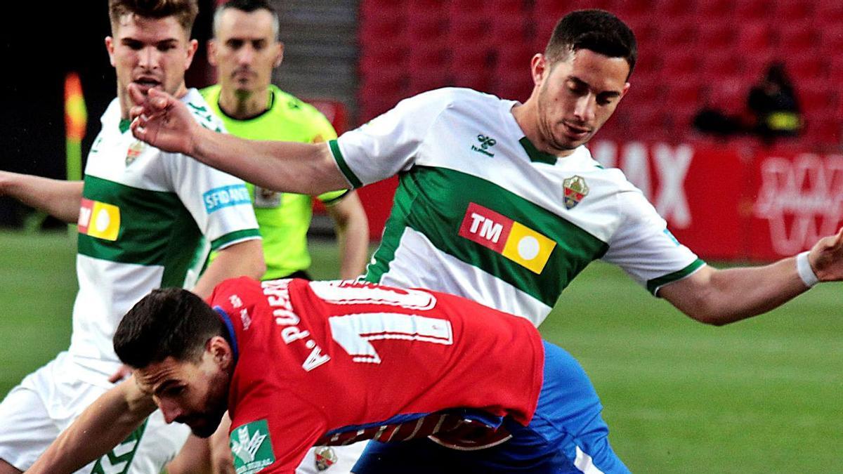 Iván Marcone intenta frenar a Antonio Puertas durante el partido del domingo en Granada.  | PEPE TORRES/EFE