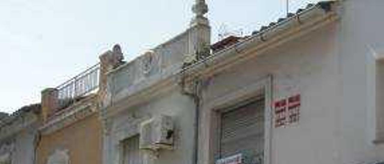 Carteles de inmobiliarias en una vivienda en Alzira.