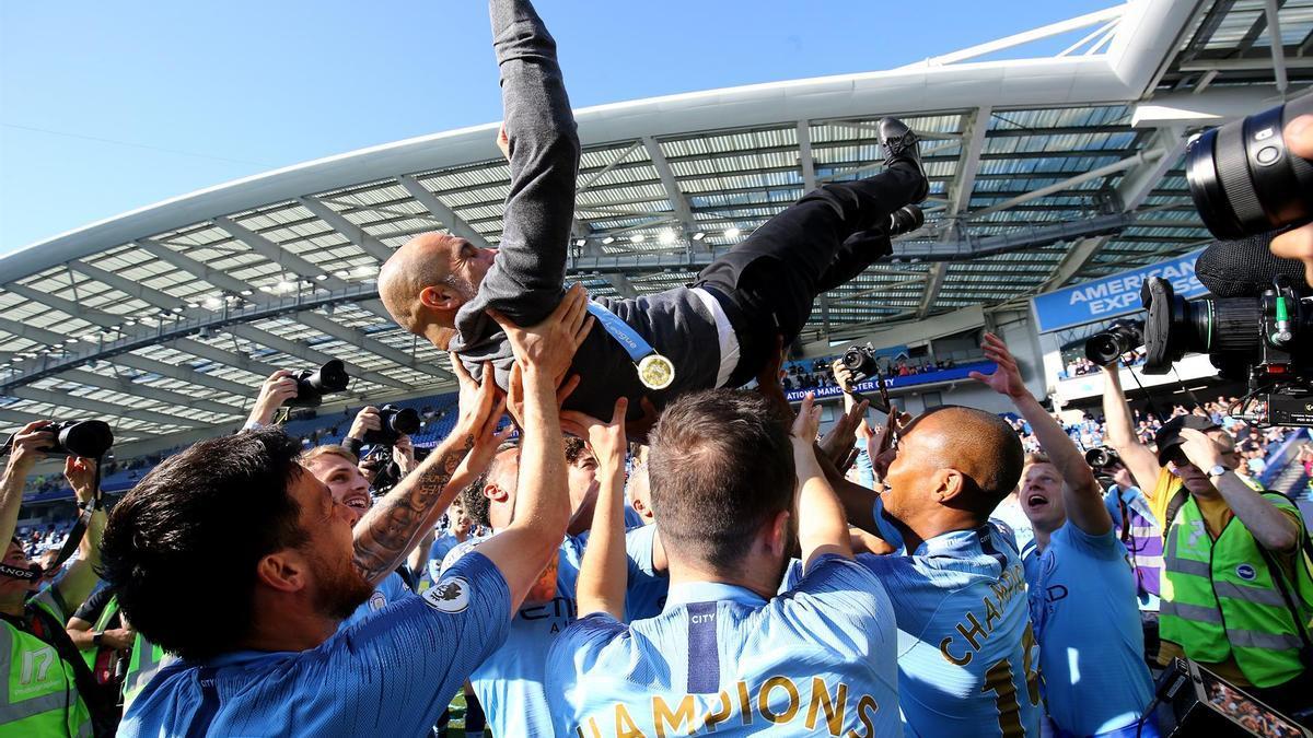 Los jugadores del Manchester City mantean a Guardiola en la celebración de un título anterior