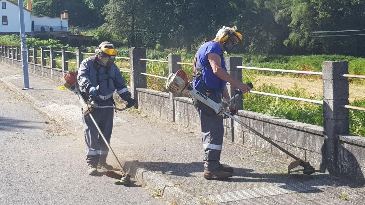 Operarios del Concello de Forcarei, ejecutando tareas de limpieza en una vía pública.