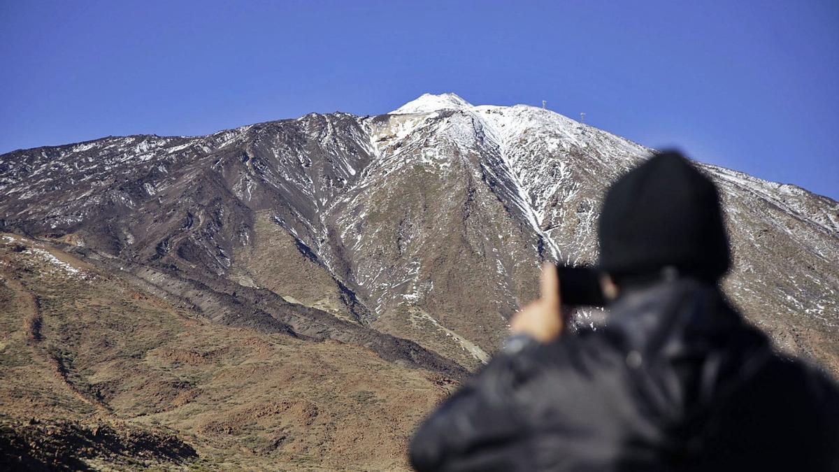 Un hombre toma una fotografía de El Teide parcialmente nevado.