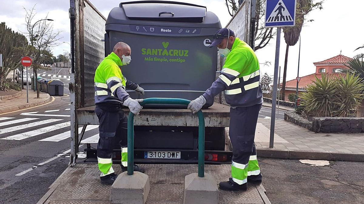 Operarios del servicio de limpieza y recogida de basura de Santa Cruz colocan un contenedor.