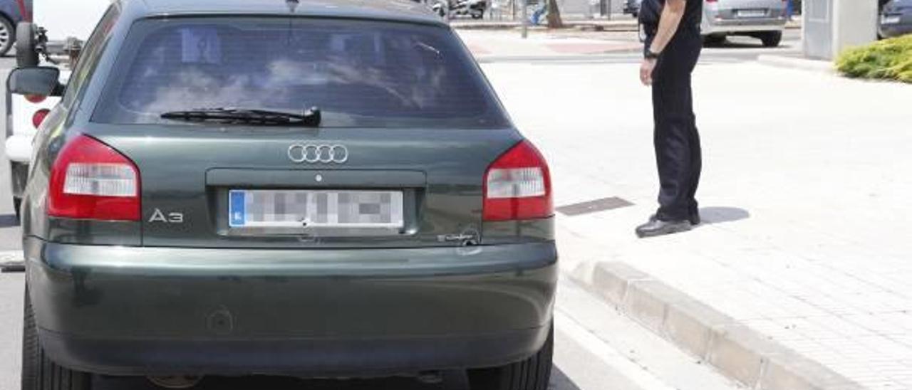 Un agente observa cómo la grúa se lleva el vehículo tiroteado en la plaza de Europa de Algemesí.