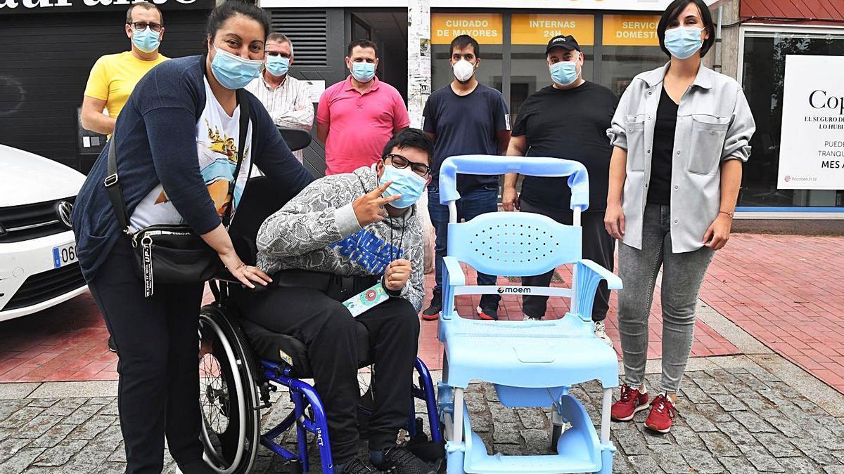 Algunos de los taxistas que colaboraron para comprar la silla, ayer, con Ezequiel y su madre.     // C. PARDELLAS